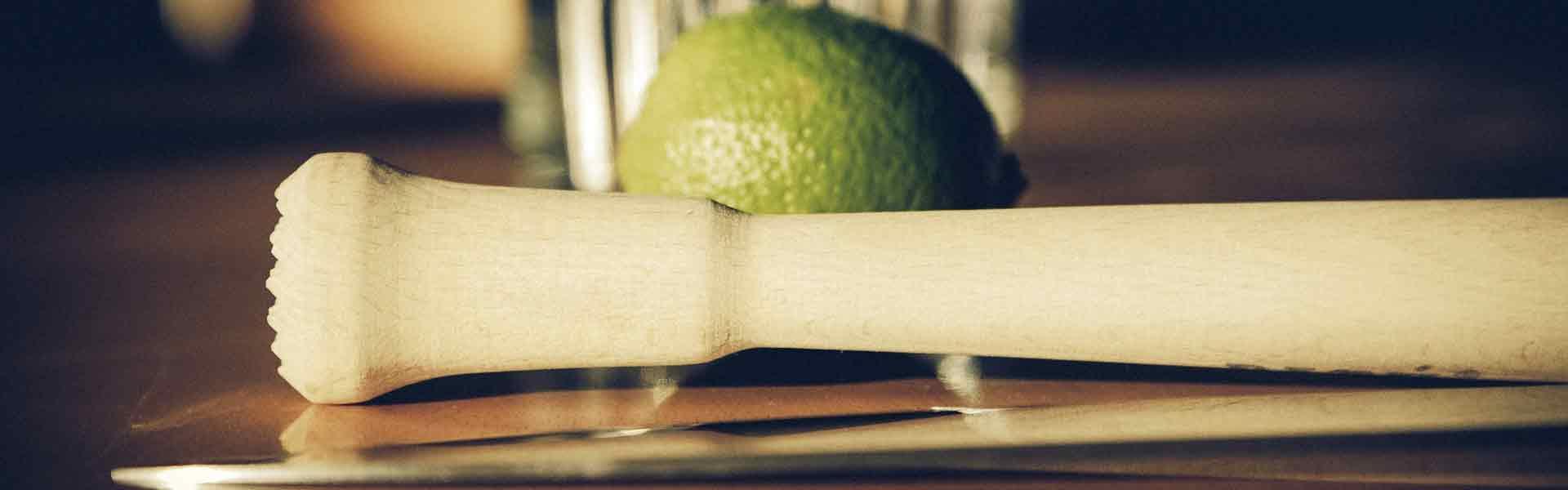 Bild einer Caipirinha mit einem Stößel im Vordergrund